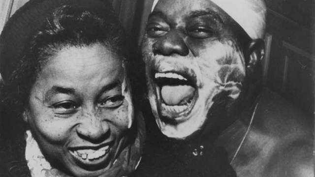 Louis Armstrong with cloth around head and shaving cream on face with Lil Hardin Armstrong; Lil was visiting Louis backstage; (another shot from this set was used in EBONY)